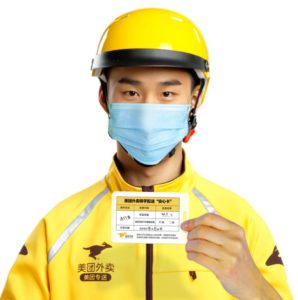 Chinese delivery driver i yellow overalls, holding a card that confirms that he doesn't have a temperature